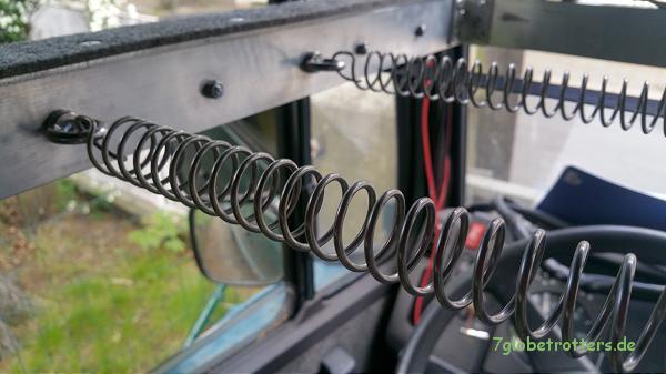 Technik im Fahrerhaus: Befestigung der Zugfedern am Rahmen des Hubbetts mit Ringschrauben